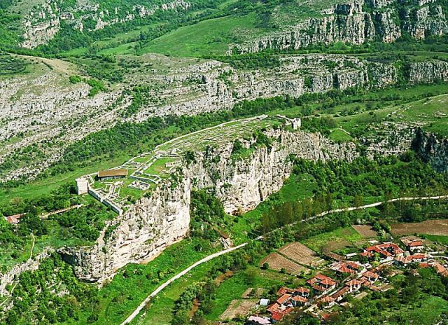 A view of the ruins of the medieval Bulgarian city of Cherven towering above the Cherni Lom River canyon, with the contemporary village of Cherven located down in the gorge. Photo by Rusenski Lom Natural Park, lomea.org