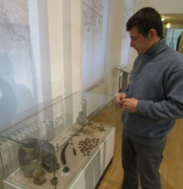 Archaeologist Varbin Varbanov looking at some of his finds from Batin and Brestovitsa in the Ruse Regional Museum of History. Photo by Ruseinfo