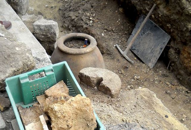 A partially compromised earthen jar and an ancient millstone (next to the jar) found in downtown Varna. Photo by Darik Varna