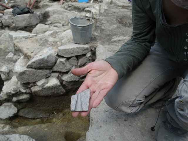 Archaeologist Elena Bozhinova shows the partially preserved stone cast used by the ancient inhabitants of Bulgaria's Plovdiv for the production of bronze spear tips. The two halves of the cast were tied together with a rope, and melted bronze was poured in the opening to make the spear tip. Photo: Pod Tepeto